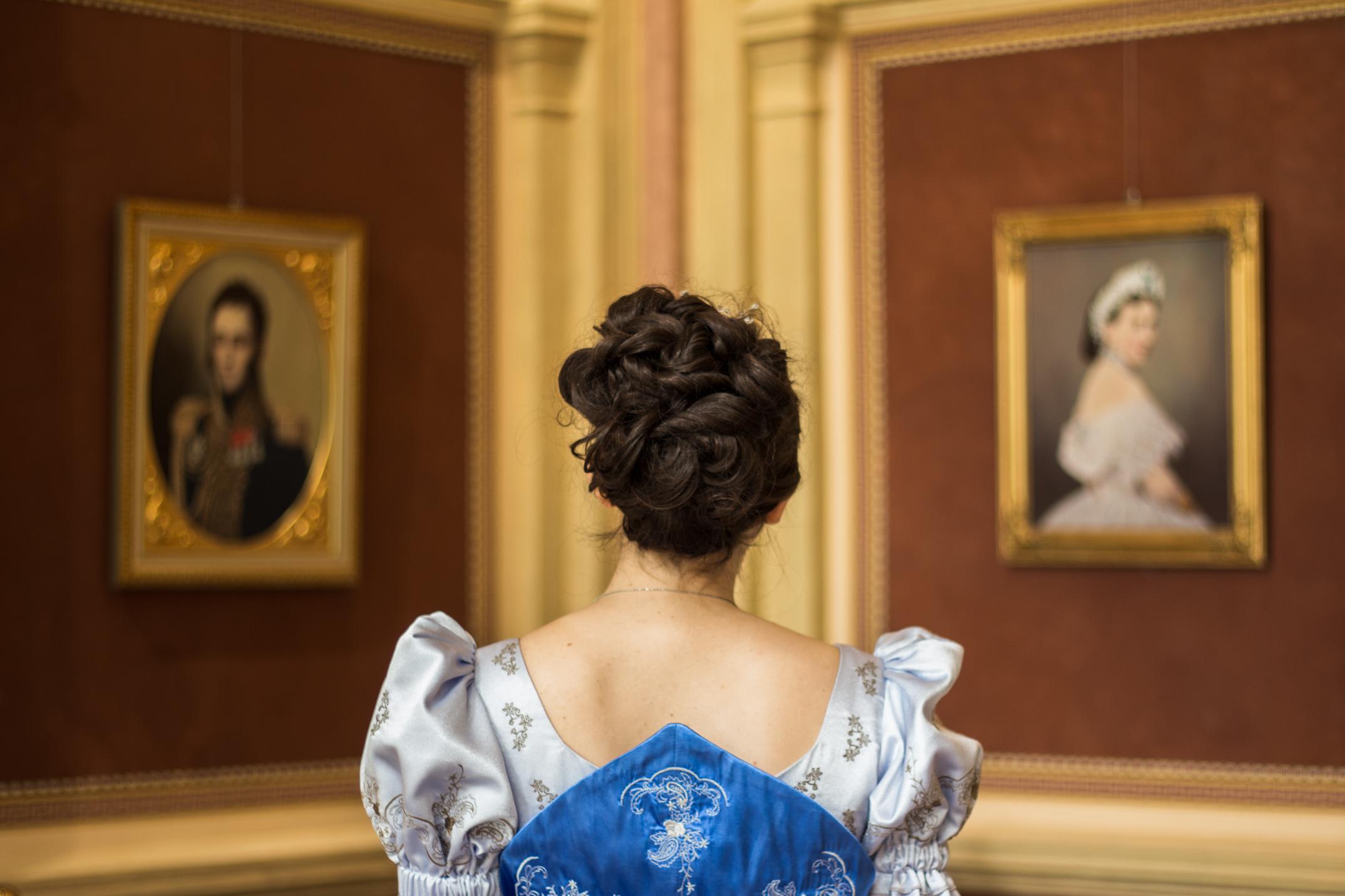 Przewodniczka w stroju historycznym ogląda ekspozycje w Oranżerii.
